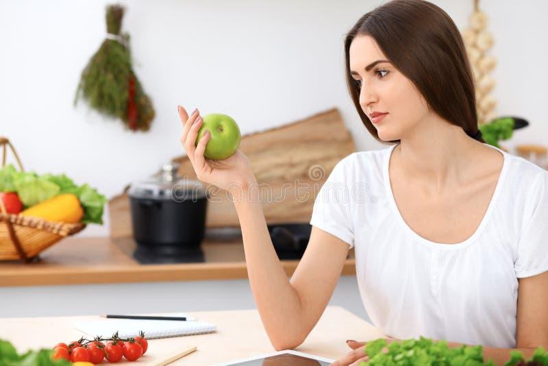 Красивая испанская женщина держит зеленое яблоко пока ищущ интернет для нового рецепта стоковое изображение