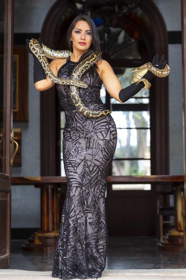 Красивая испанская модель брюнета представляет со змейкой Constrictor горжетки вокруг ее тела стоковая фотография