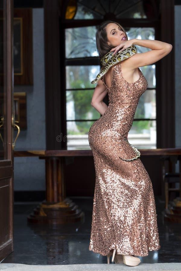Красивая испанская модель брюнета представляет со змейкой Constrictor горжетки вокруг ее тела стоковые фото