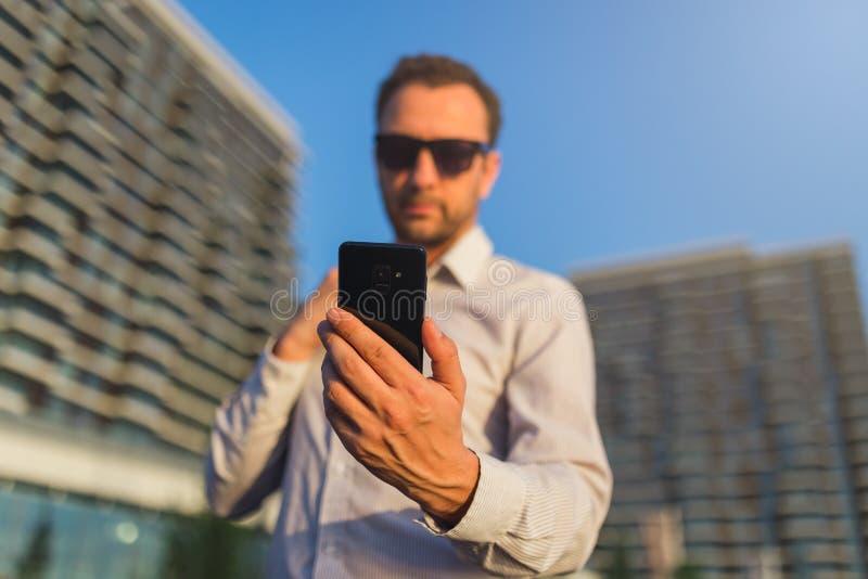 Красивая исполнительная власть смотря его смартфон против современных зданий стоковое изображение