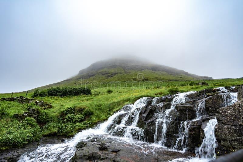 Красивая и мирная долгая выдержка водопада с зеленой травой и небольшими домами в туманной погоде в деревне Bour, Фарерскими остр стоковое фото rf