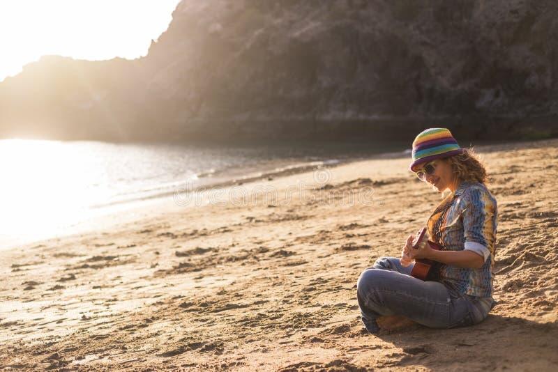 Красивая и мирная молодая женщина сидя на береге на досуге пляжа anjoying на песке играя гавайскую гитару стоковые изображения rf
