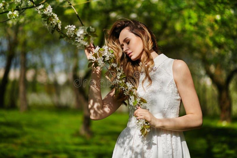 Красивая и модная молодая белокурая женщина в белом платье представляя outdoors в парке стоковые фотографии rf