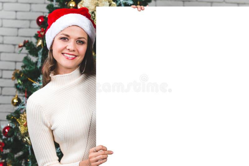 Красивая и молодая кавказская женщина держа и указывая на blan стоковая фотография rf