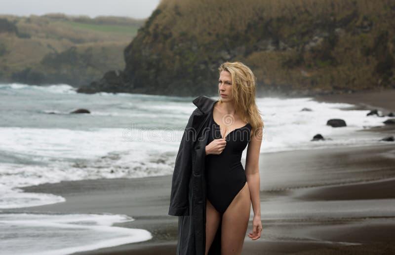 Красивая и сексуальная белокурая женщина в черном купальнике с кожаной курткой на пляже стоковое изображение rf
