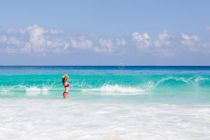 Красивая и сексуальная белокурая женщина в красном купальнике на тропическом пляже, Сейшельских островах стоковые фотографии rf