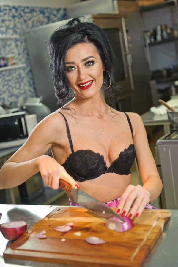 Красивая и сексуальная женщина в кухне Усмехаясь брюнет подготавливая еду Маленькая девочка нося черный бюстгальтер режа некоторы стоковое фото