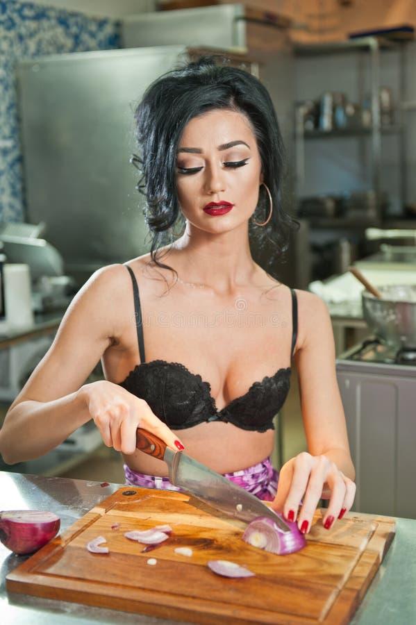 Красивая и сексуальная женщина в кухне Усмехаясь брюнет подготавливая еду Маленькая девочка нося черный бюстгальтер режа некоторы стоковое фото rf