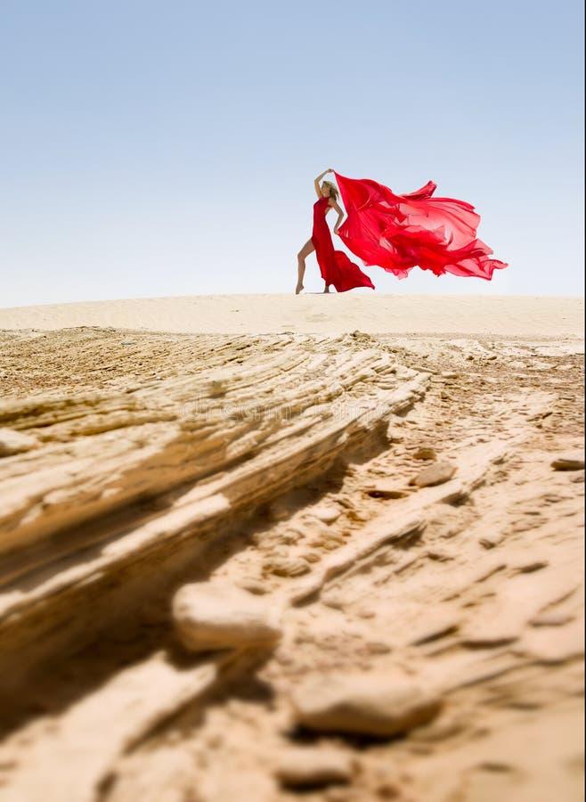 Красивая и сексуальная тонкая женщина, красное платье в пустыне стоковое фото