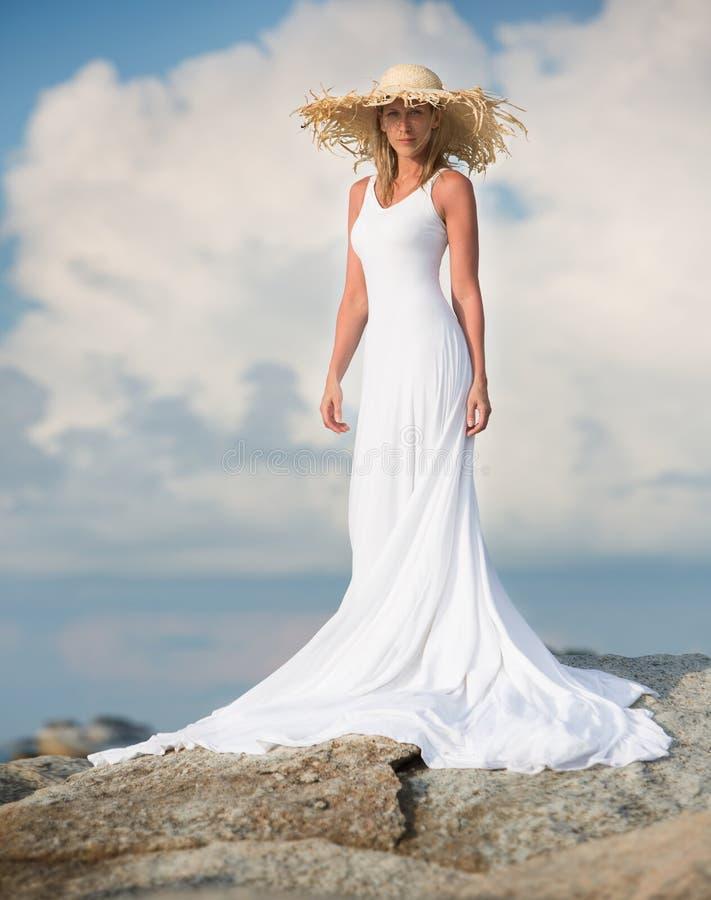 Красивая и тонкая стойка женщины в белом длинном платье стоковые изображения rf