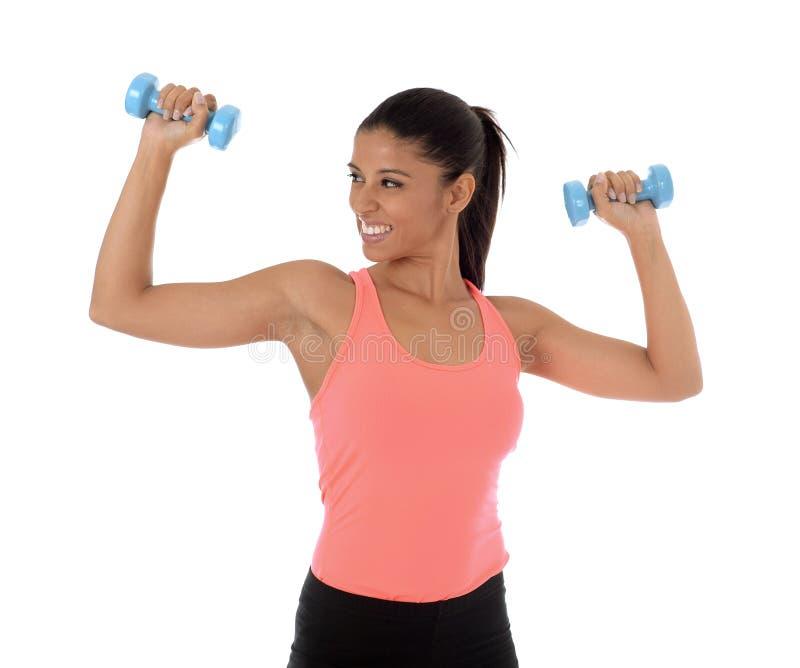 Красивая и экзотическая испанская женщина держа руку утяжеляет тренировку в концепции фитнеса стоковое изображение rf