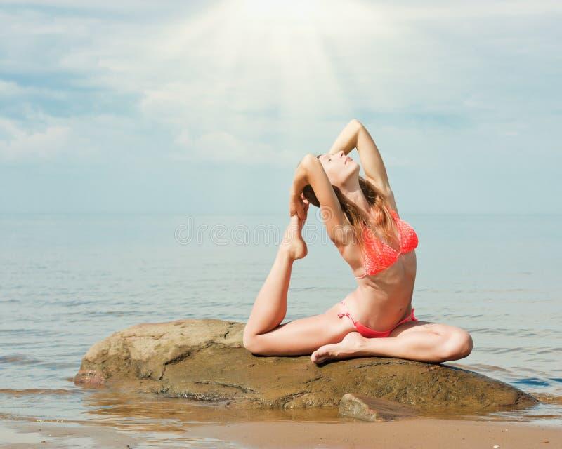Красивая йога женщины на пляже стоковое фото