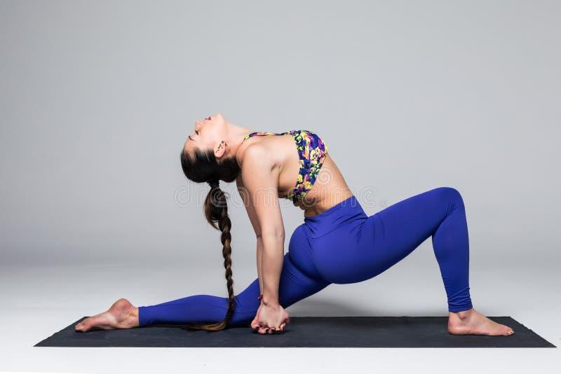 Красивая йога практики женщины йоги представляет на серой предпосылке стоковые фотографии rf