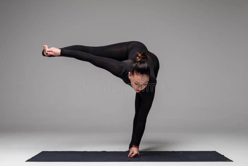 Красивая йога практики женщины йоги представляет на серой предпосылке стоковые изображения rf