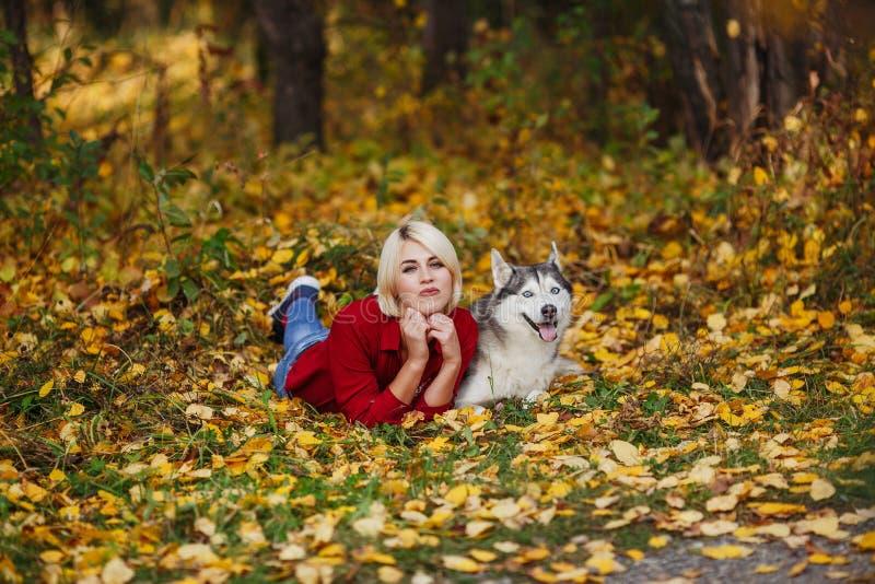 Красивая кавказская девушка играет с осиплой собакой в лесе осени стоковое изображение rf