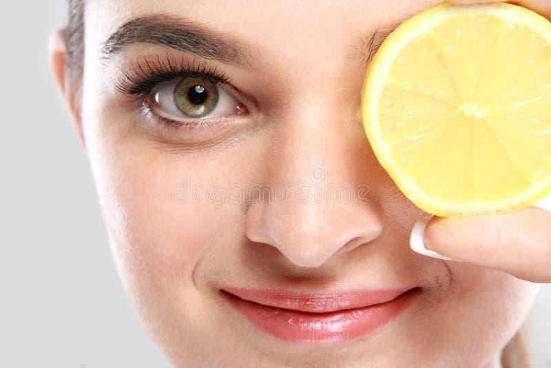Красивая кавказская женщина держа кусок лимона стоковое изображение