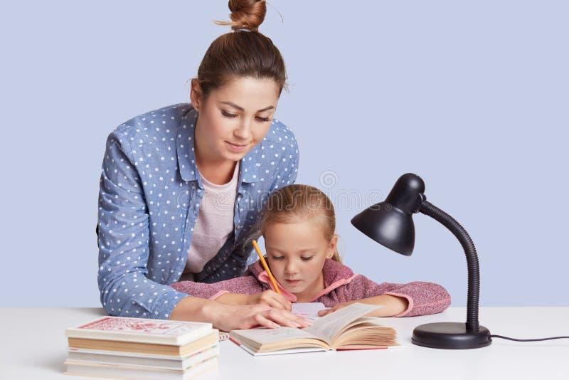 Красивая кавказская женщина помогая ее doughter для того чтобы сделать домашнюю работу школы, мать и ребенка surronded книгами, с стоковые изображения