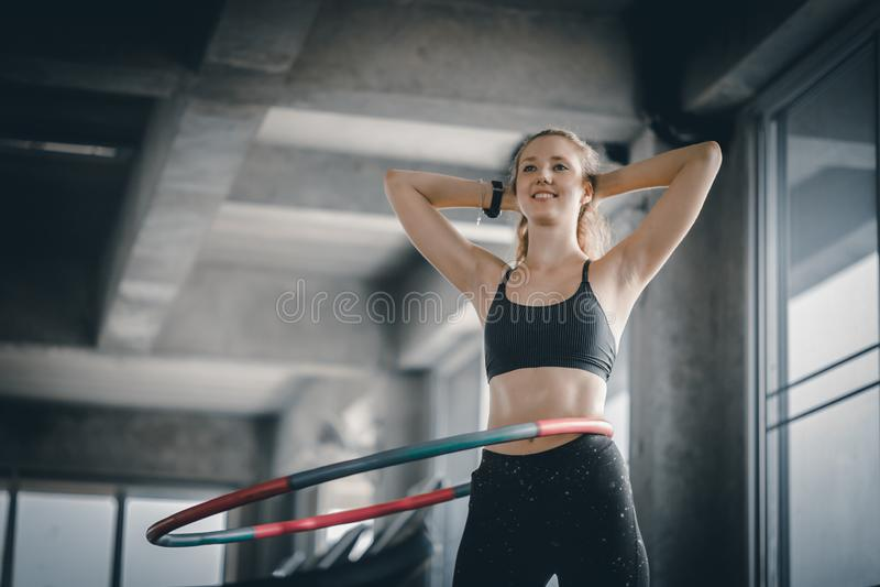 Красивая кавказская молодая женщина делая обруч hula в талии шага hooping передняя позиция Молодая женщина делая обруч hula стоковые фотографии rf