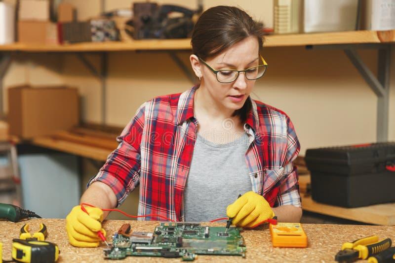 Красивая кавказская молодая женщина коричнев-волос работая в мастерской плотничества на месте таблицы стоковые фото