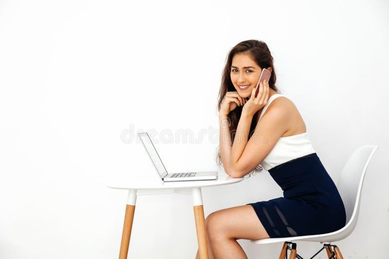 Красивая кавказская усмехаясь женщина говоря на телефоне пока использующ компьтер-книжку на белом столе над белизной изолировала  стоковые изображения