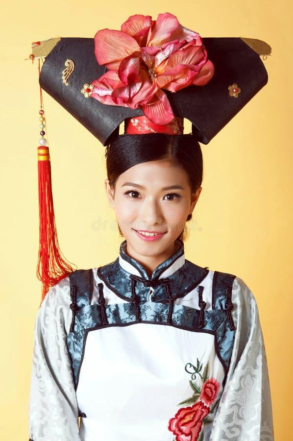 Красивая китайская женщина нося традиционное обмундирование против желтой предпосылки стоковые изображения
