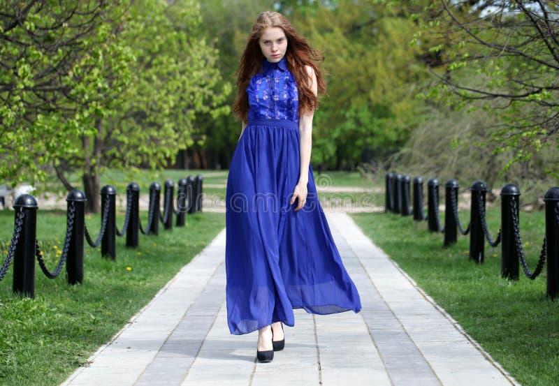 Красивая красная девушка волос в голубом платье стоковое фото rf