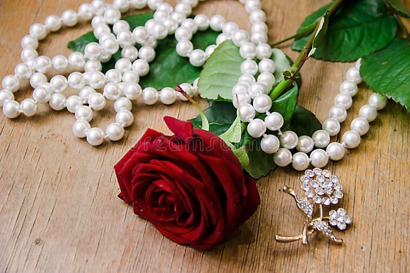 Красивая красная роза с жемчугом отбортовывает на бежевой предпосылке стоковые фотографии rf