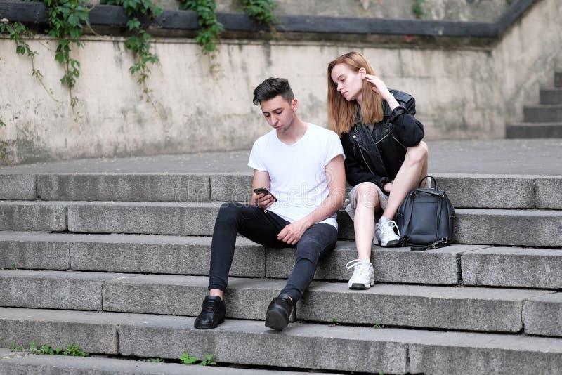 Красивая красная с волосами девушка и парень брюнет увидели что-то интересное в их мобильном телефоне стоковое изображение