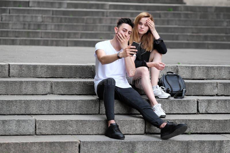 Красивая красная с волосами девушка и парень брюнет увидели что-то интересное в их мобильном телефоне стоковые изображения