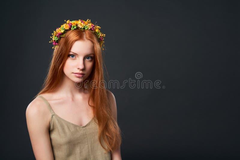 Красивая красная с волосами женщина в венке цветка стоковые фотографии rf