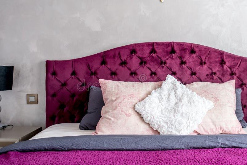 красивая кровать в элегантной и удобной современной спальне с фиолетовыми постельными принадлежностями Детали дизайна интерьера стоковые фотографии rf