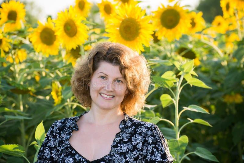 Красивая курчавая женщина в поле солнцецветов стоковое изображение rf
