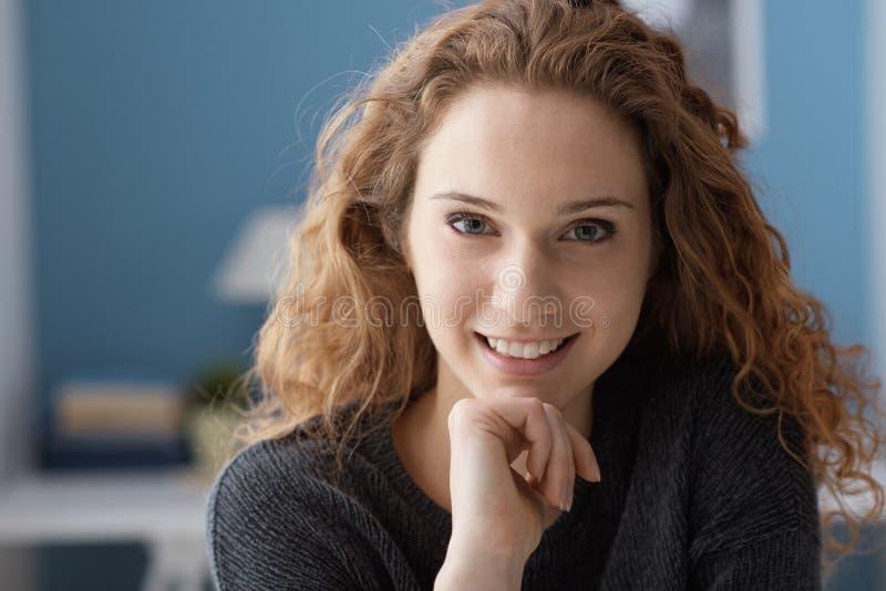 Красивая курчавая молодая женщина представляя дома стоковое изображение rf
