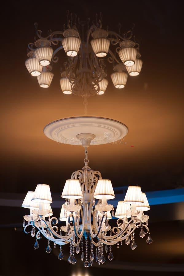Красивая люстра при включении несколько ламп темный потолок стоковое фото