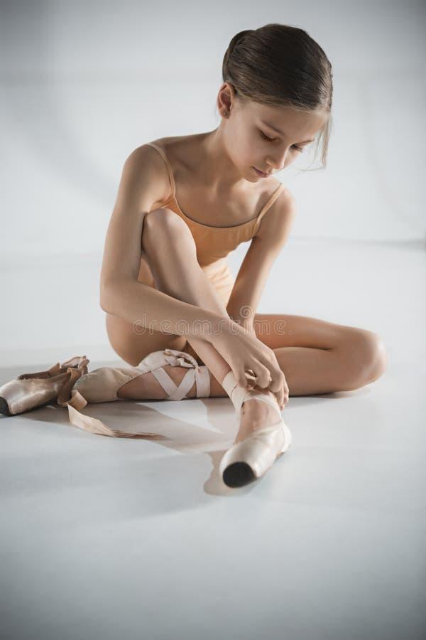 Красивая маленькая балерина кладя пешком ботинки pointe стоковая фотография