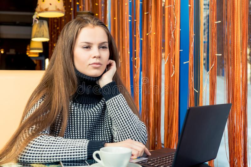 Красивая маленькая девочка в деятельности кафа с ноутбуком и выпивая co стоковая фотография
