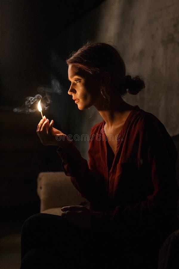 Красивая маленькая девочка в красных светах рубашки вверх ее милая сторона со спичкой сидя в темной комнате и держа matchbox в ру стоковая фотография rf