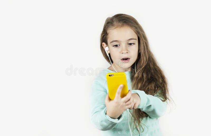 Красивая маленькая девочка в наушниках с телефоном в ее руках эмоционально говорит и радуется на изолированной предпосылке стоковые изображения