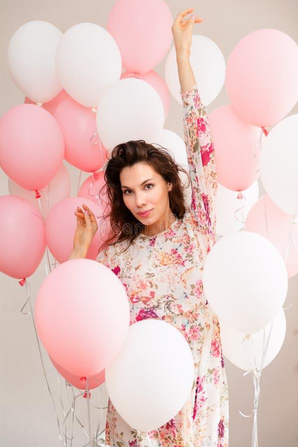 Красивая маленькая девочка в платье с воздушными шарами на дне рождения Портрет милой женщины с пестротканым воздушным шаром брюн стоковые изображения rf