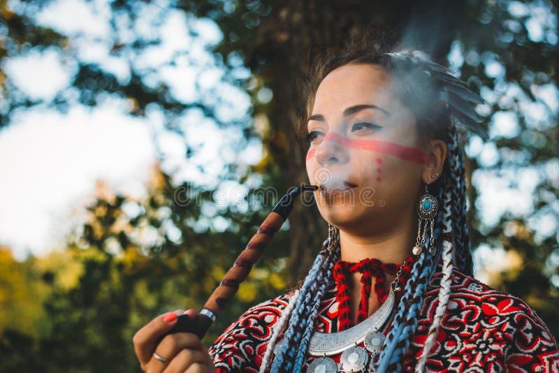 Красивая маленькая девочка в платье трубы коренных американцев куря стоковые фотографии rf