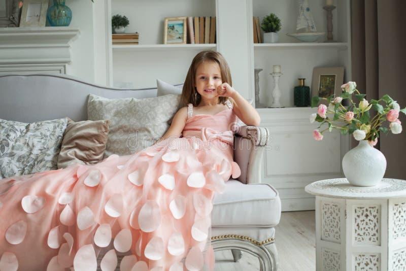 Красивая маленькая девочка в розовом платье дома стоковые изображения