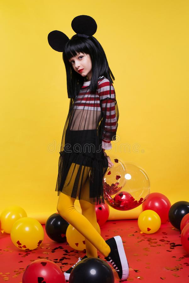 Красивая маленькая девочка в черном парике представляя над яркой желтой предпосылкой стоковое изображение