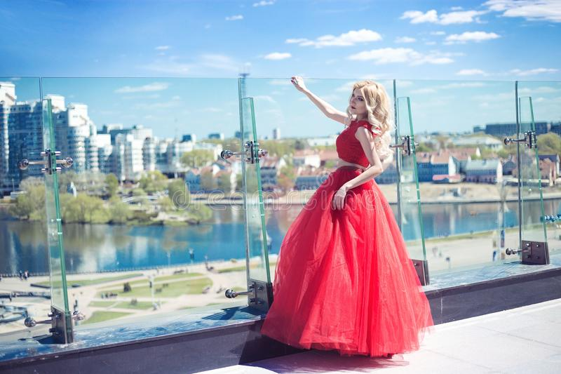 Красивая маленькая девочка на крыше здания в красном сочном платье стоковая фотография rf