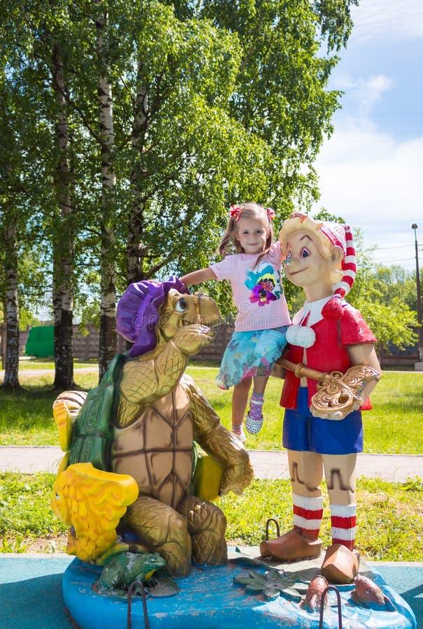 Красивая маленькая девочка на спортивной площадке с Pinocchio и черепахой стоковые фотографии rf