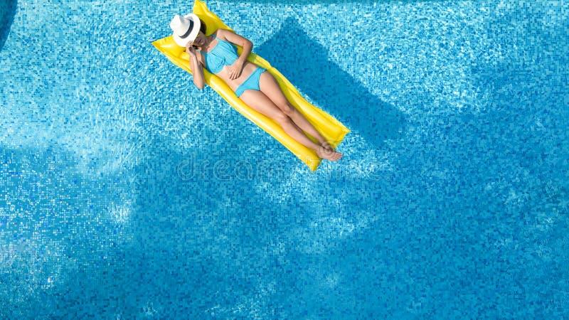 Красивая маленькая девочка ослабляя в бассейне, плавает на раздувном тюфяке и имеет потеху в воде на семейном отдыхе стоковая фотография rf