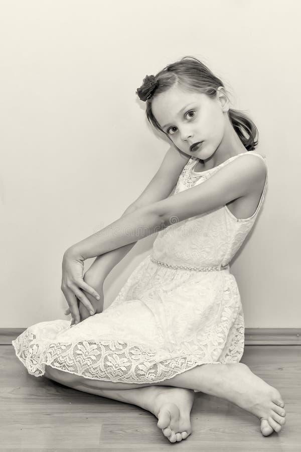 Красивая маленькая девочка представляет сидеть на поле стоковая фотография rf