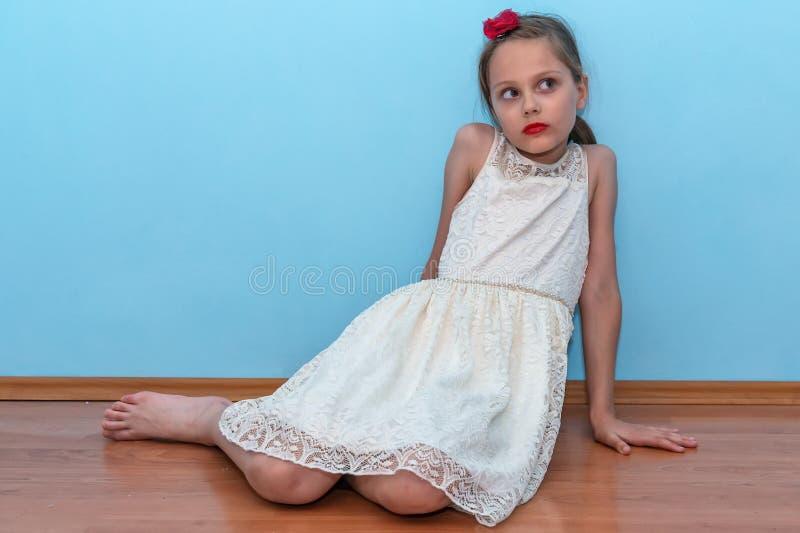 Красивая маленькая девочка представляет сидеть на поле стоковые изображения