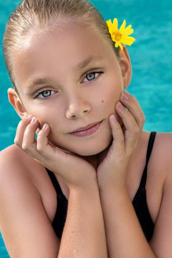 Красивая маленькая девочка, маленькая принцесса с белокурыми волосами с стилем причёсок плюшки и с желтым цветком в волосах, стоя стоковые изображения rf