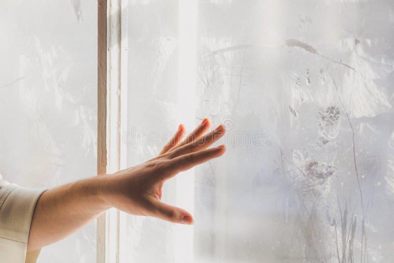 Красивая маленькая девочка рисует на замороженном окне стоковая фотография