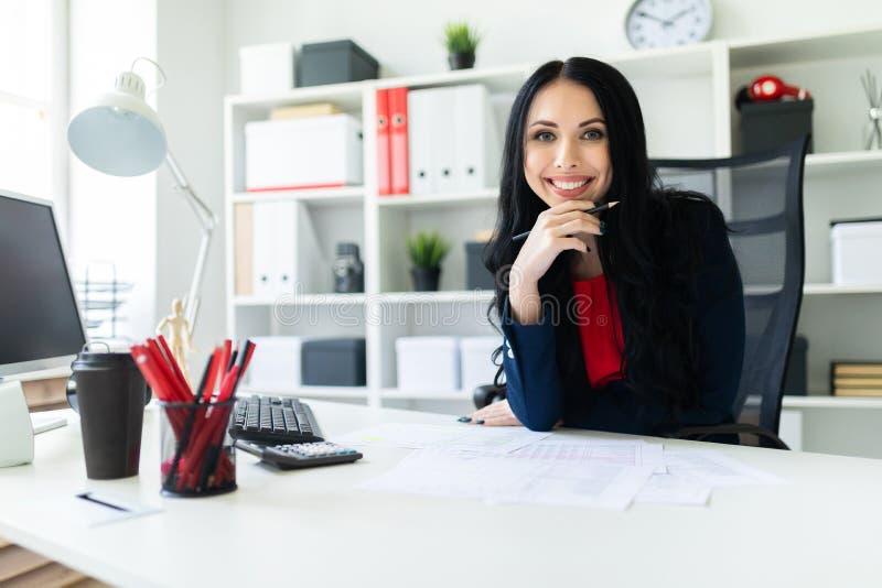 Красивая маленькая девочка сидит в офисе на таблице и держит карандаш в ее руке стоковое фото
